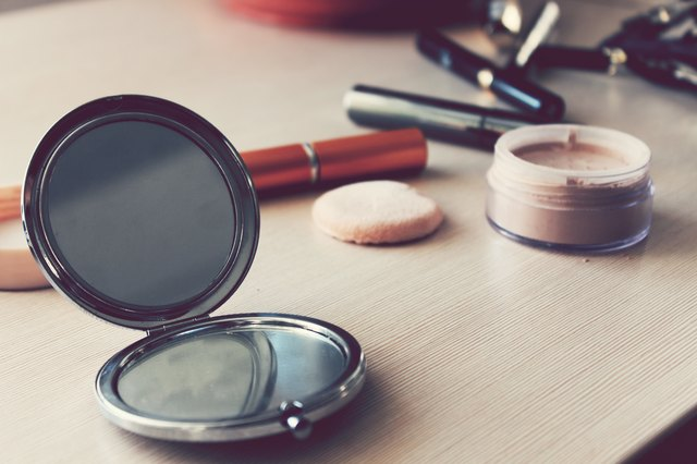 Mirror, powder and other cosmetics on the table