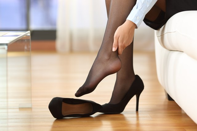 Woman rubbing sore feet after wearing high heels
