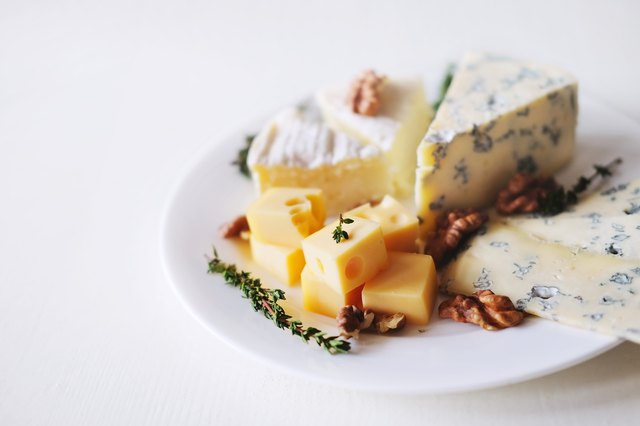 Cheese plate with different kinds of cheese with thyme herbs and walnuts