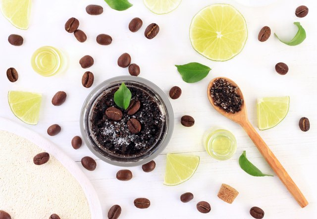 Cosmetic jar of homemade coffee based scrub, with fresh citrus essential oil