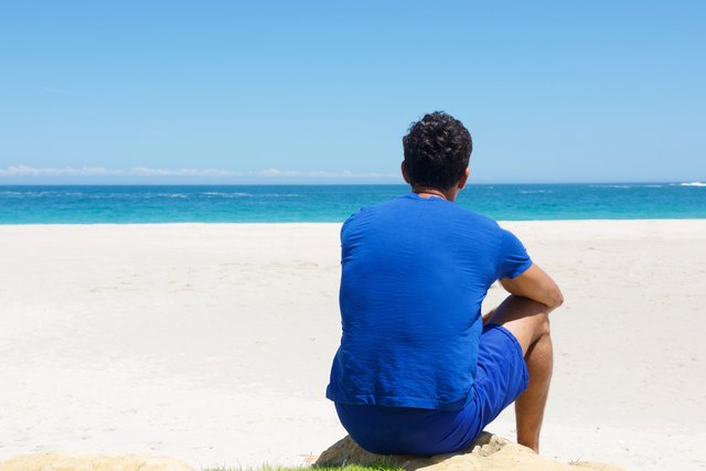 Man wearing blue in the sun at the beach