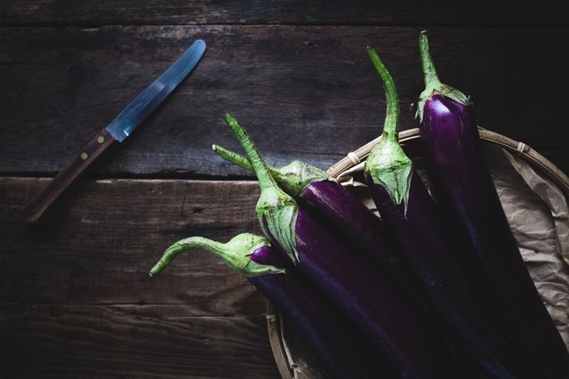 Directly Above Shot Of Eggplants In Basket By Knife On Wooden Table