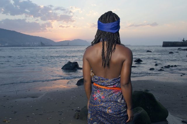 African woman at sunset near the beach.