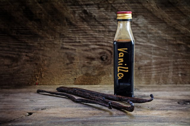 vanilla extract in a bottle and pods on rustic wood