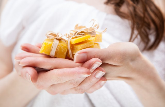 Woman hands holding pieces of beeswax