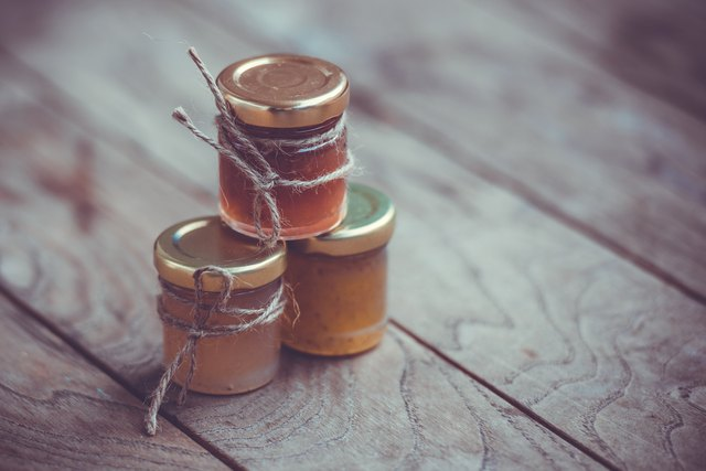 Jars of marmalade wrapped in twine on a wooden table