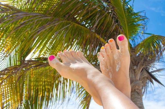 Woman's beauty legs with fashion pedicure at beach