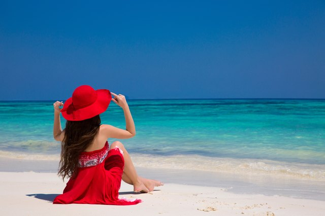Happy woman enjoying beach relaxing joyful on white sand