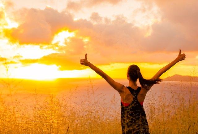 Sporty girl raising arms towards beautiful glowing sunshine.