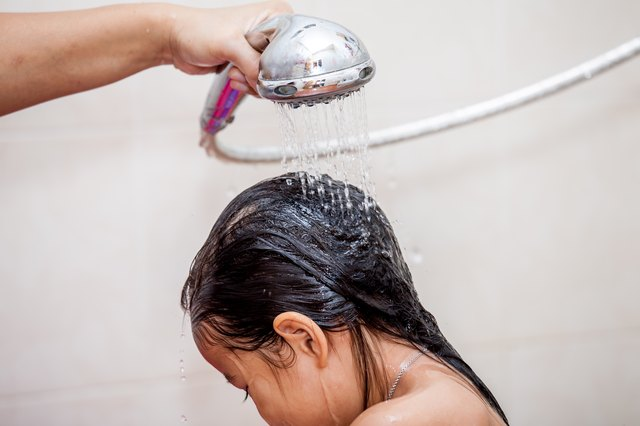 Mother's hand pours water from shower to wash hair