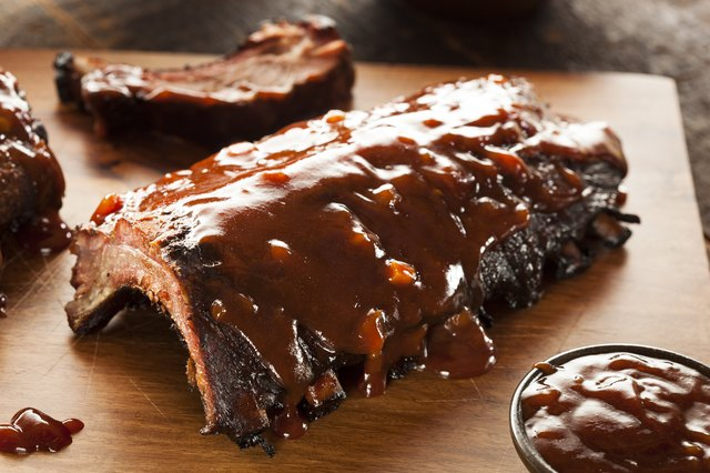 A close-up of smoked barbecue pork spare ribs on wood