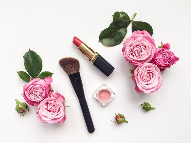 Decorative flat lay composition with cosmetics and flowers. Top view