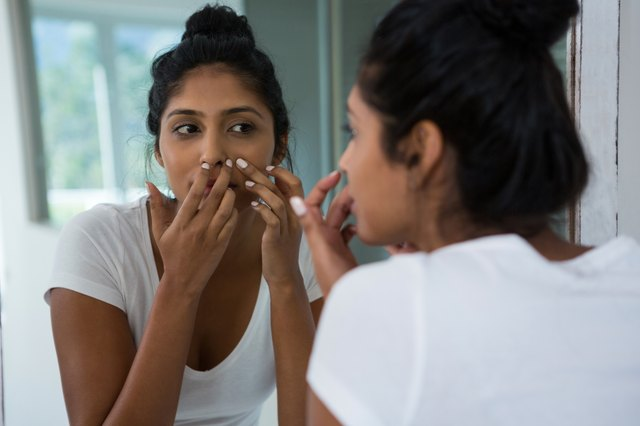 Woman squeezing pimple reflecting on mirror