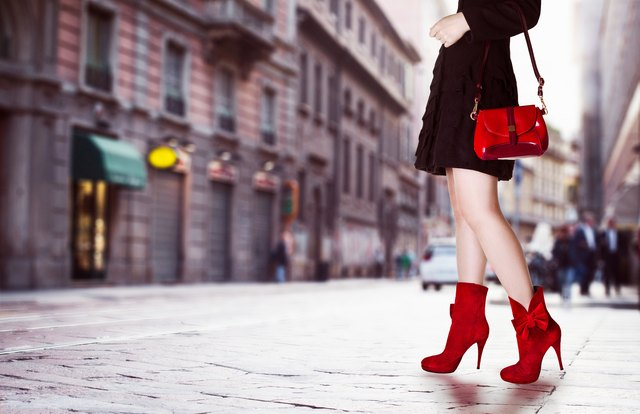 Girl with red bag and red boots in the street.