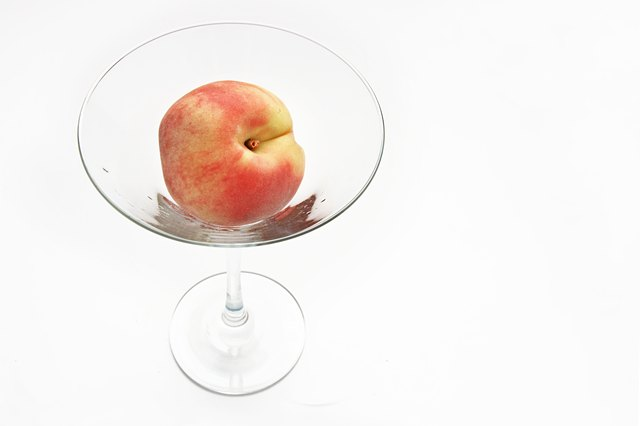 Fresh peach in the martini glass isolated on white background