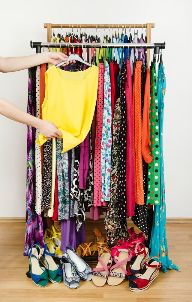 Woman hand picking up a yellow blouse to wear.