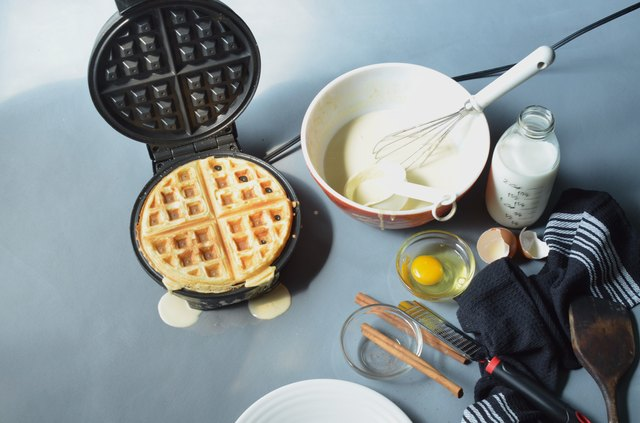 Waffle in open waffle iron, cinnamon grated from cinnamon sticks,