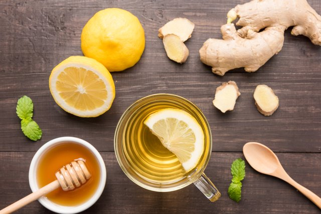 Cup of ginger tea with lemon and honey on table.