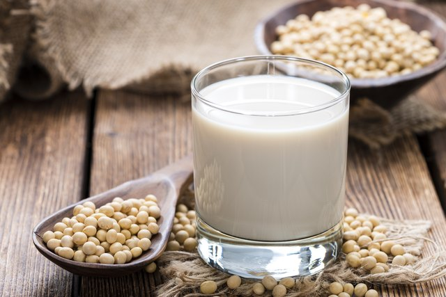 Soy beans on a wooden table with a glass of milk on the side