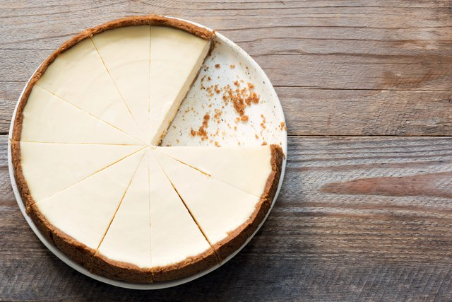 New York Cheesecake or Classic Cheesecake sliced on rustic wood, top view
