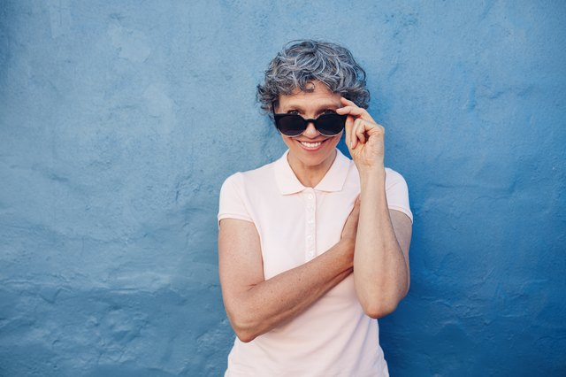 Smiling mature woman peeking over sunglasses