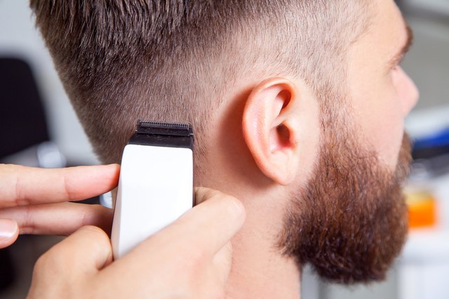 Barber cutting hair with electric clippers
