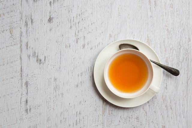 Cup of tea with spoon on white background