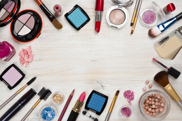 Makeup products on wooden background with copy space in center