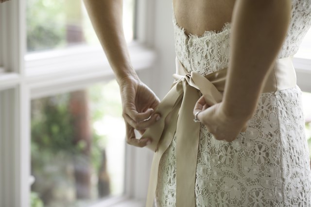 Woman tying a cream-colored bow on a white dress