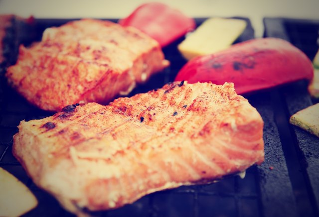 Salmon steaks being fried on grill, toned