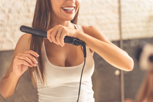 Beautiful woman using a straightening iron