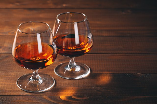 Two glasses of cognac on the wooden table.