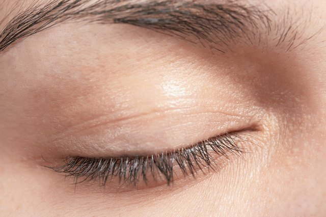 Close-up of woman's eyelid including eyelashes and eyebrow