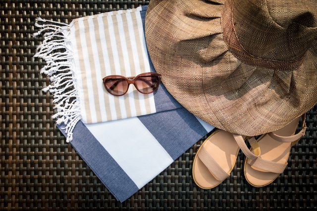The concept of flatlay summer accessories of white, blue and beige Turkish towel, sunglasses, beige leather ladies sandals and straw hat on a rattan lounger.