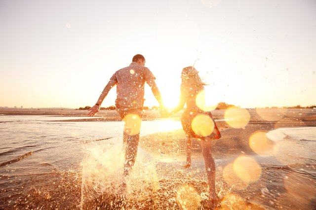 A happy couple runs through waves on sunlit beach