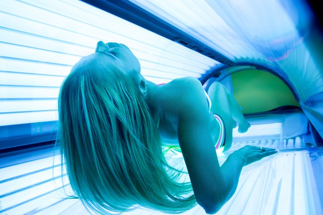Woman with long hair in a tanning bed