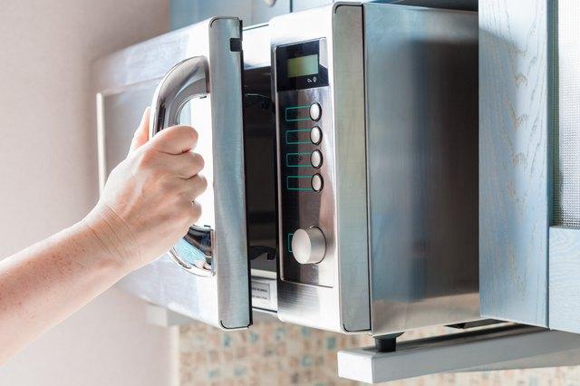 hand opens microwave oven door
