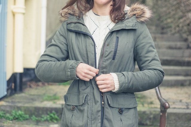 Young woman buttoning her coat outside