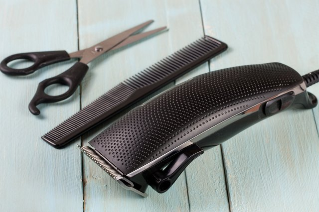 hair clippers with comb and scissors on wooden background
