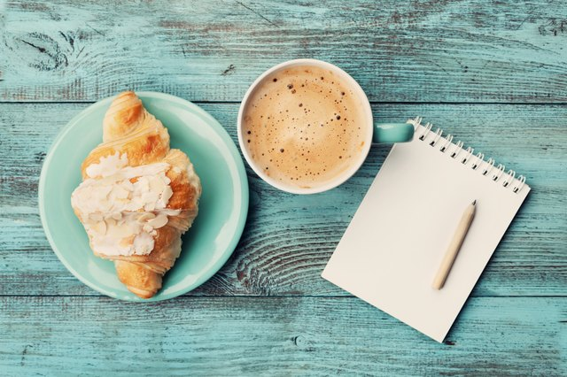 Coffee with croissant and notebook for business plan and design