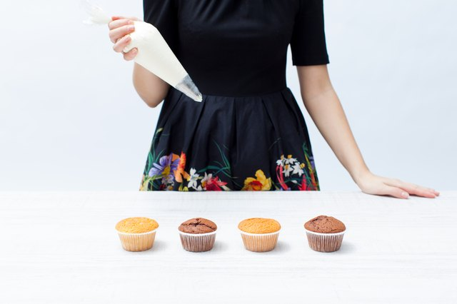 Girl chef with piping bag with the cream, cupcakes