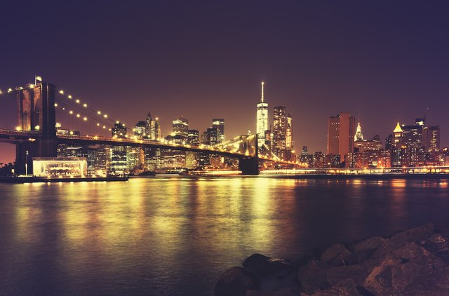 Retro toned New York waterfront at night, USA.