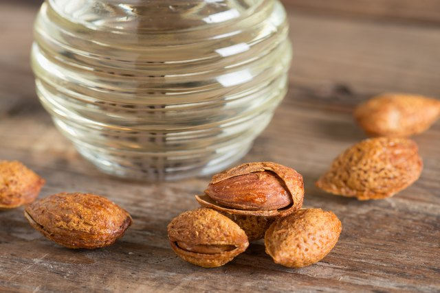 Close up, Almond kernel with bottle almonds oil.
