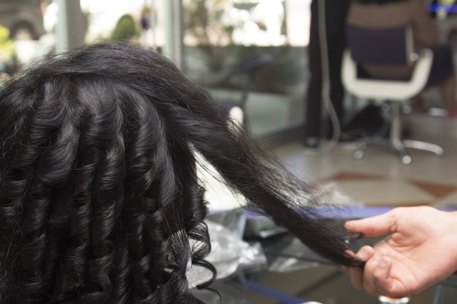 client with black curly hair at hairdresser