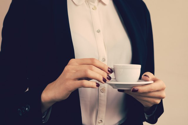 Woman in white blouse and black jacket holding a coffee