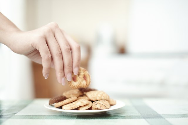 Woman get some cookie from the table