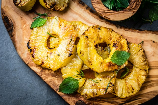 Grilled pineapple slices with fresh mint on olive cutting board