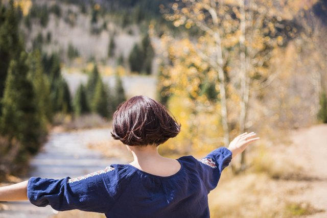 Young woman running towards Mineral Creek in Colorado