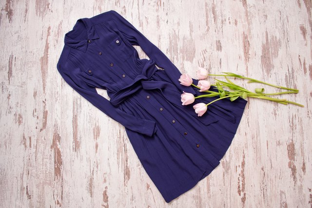 Blue dress with buttons and pink tulips. Wooden background. Fashionable concept. View from above