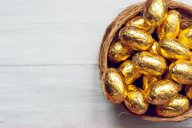 Golden easter eggs  - chocolate eggs in nest, on white wooden background